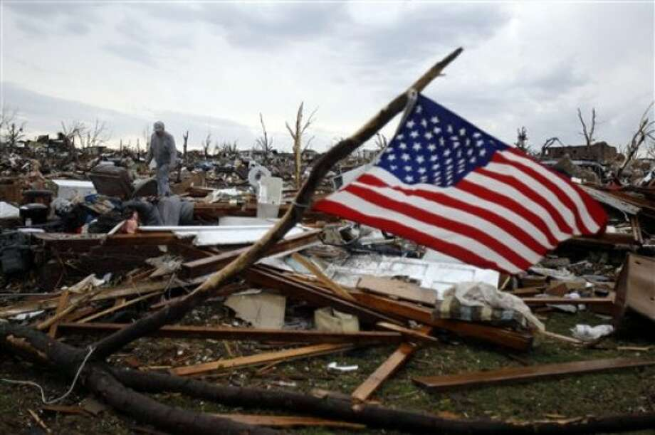 Josh Ramsey looks through the rubble of what is left of his mother-in-law''s home following a tornado Monday, May 23, 2011, in Joplin , Mo. A massive tornado that tore a six-mile path across southwestern Missouri killed at least 89 people as it smashed the city of Joplin, ripping into a hospital, crushing cars like soda cans and leaving behind only splintered tree trunks where entire neighborhoods once stood. (AP Photo/Jeff Roberson)