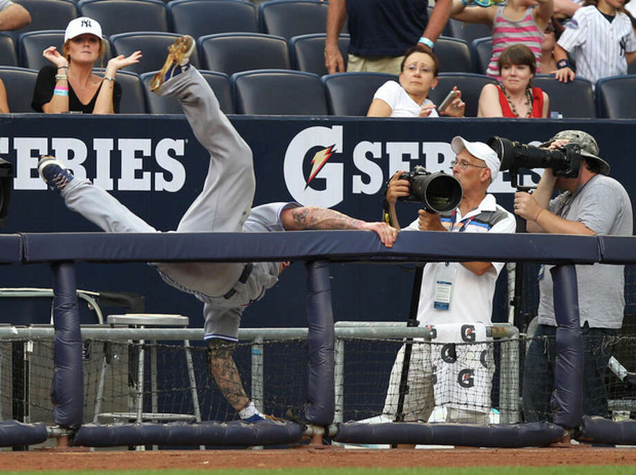Toronto Blue Jays third baseman Brett Lawrie falls into a photo well while diving for a foul ball during the third inning of the baseball game against the New York Yankees Wednesday, July 18, 2012 at Yankee Stadium in New York. Lawrie did not make the catch. (AP Photo/Seth Wenig) / AP