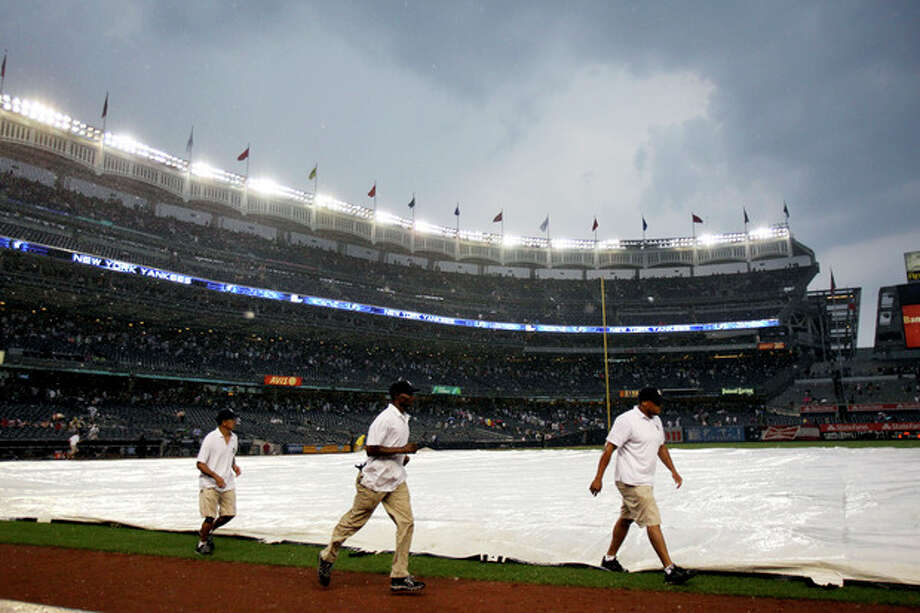 The grounds crew covers the field during a rain delay in the seventh inning of a baseball game between the New York Yankees and Toronto Blue Jays, Wednesday, July 18, 2012, at Yankee Stadium in New York. (AP Photo/Seth Wenig) / AP