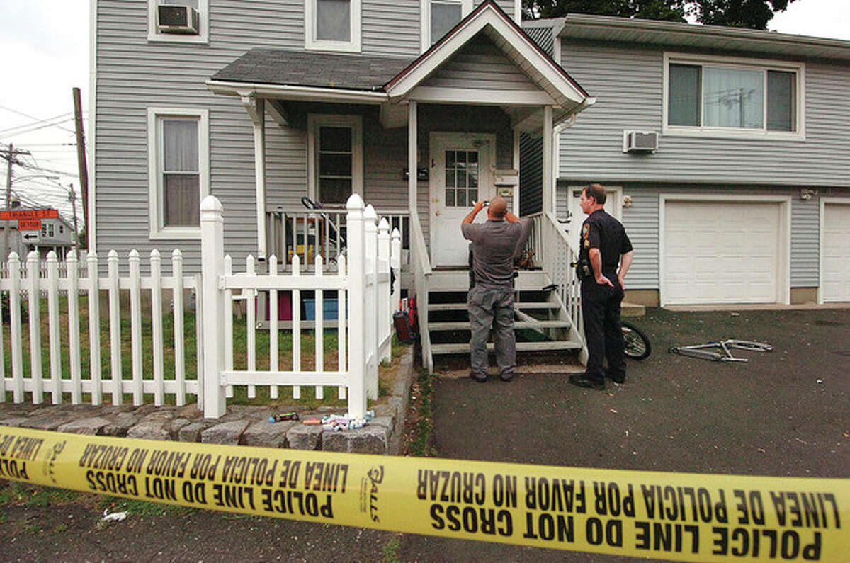 Hour photos / Alex von Kleydorff Norwalk Police and detectives photograph evidence at a house on Charles Street in Norwalk, where a stabbing occurred late Wednesday afternoon. Residents do not think the victim lived in the area.