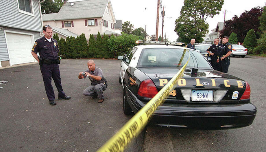 Norwalk Police and detectives investigate the scene of a stabbing on Charles Street in Norwalk. / 2012 The Hour Newspapers