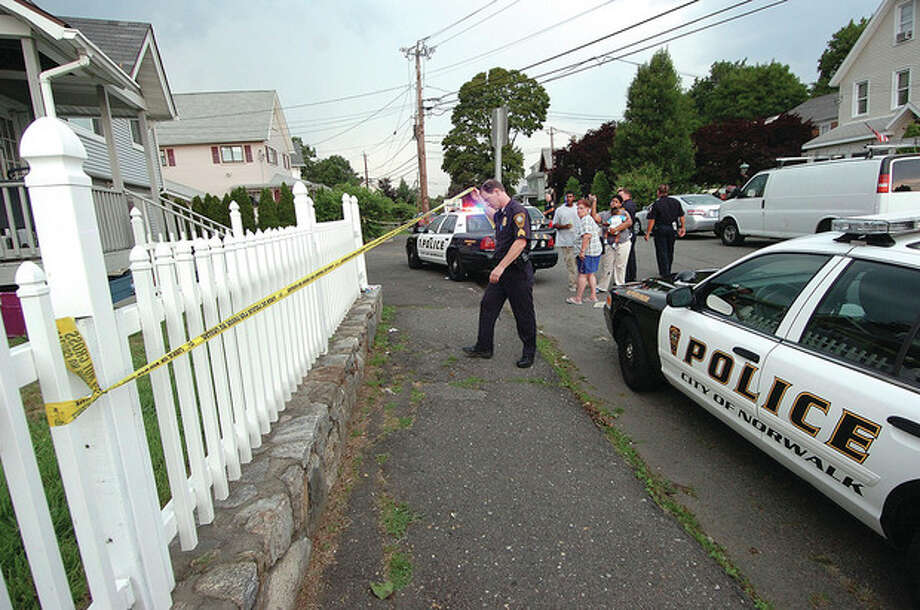 Hour photo / Alex von KleydorffNorwalk Police and detectives investigate a stabbing on Charles Street in Norwalk late Wednesday afternoon as neighborhood residents gather. / 2012 The Hour Newspapers