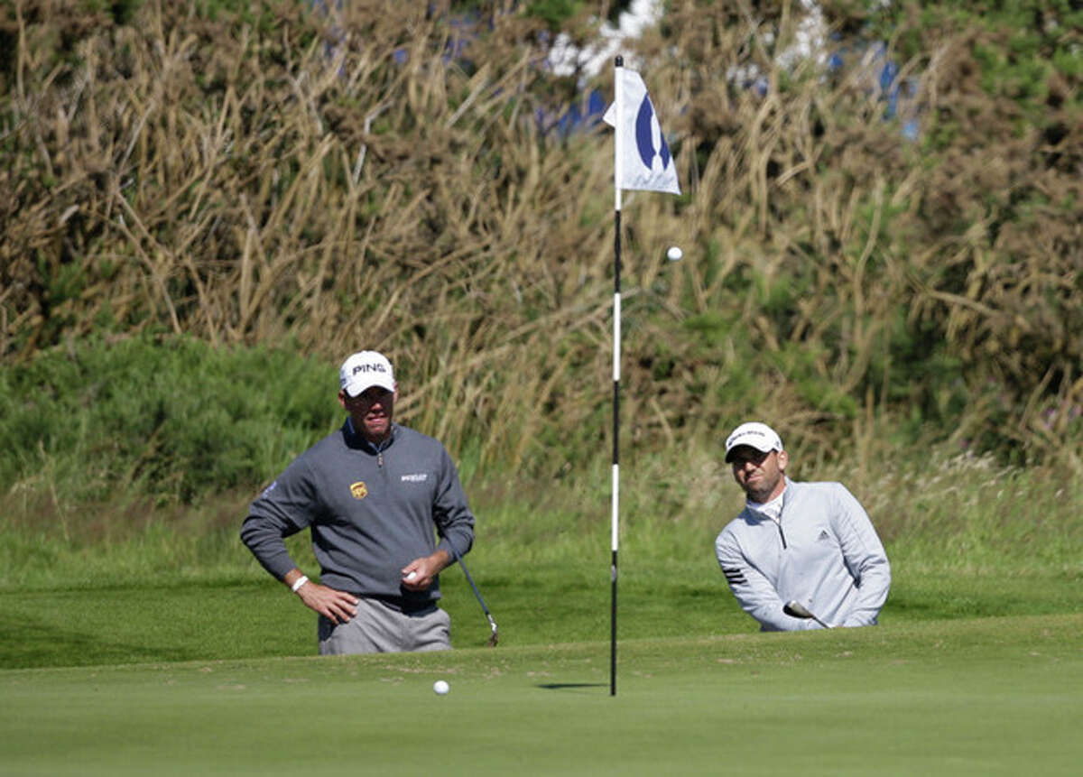 Lee Westwood of England, left, looks on as Sergio Garcia of Spain plays out of the bunker on the 17th green during a practice round at Royal Lytham & St Annes golf club ahead of the British Open Golf Championship, Lytham St Annes, England, Wednesday, July 18, 2012. (AP Photo/Tim Hales)