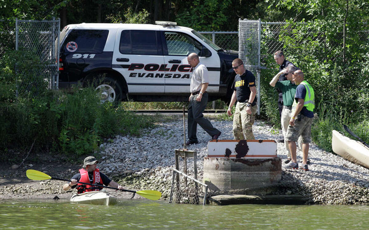 Law enforcement authorities look for possible evidence at Meyers Lake where Lyric Cook-Morrissey, 10, and Elizabeth Collins, 8, disappeared last Friday, Tuesday, July 17, 2012, in Evansdale, Iowa. The girls' bikes were found Friday afternoon near a bike trail at the edge of the lake. (AP Photo/Charlie Neibergall)