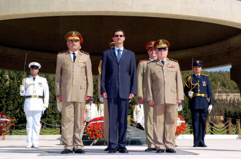 FILE - In this Thursday, Oct. 6, 2005 file photo, Syrian President Bashar Assad, center, Syrian Defense Minister Maj. Gen. Hassan Turkmani, left, and Ali Habib, the Syrian Chief of Staff, during a visit to the tomb of the unknown soldier in Damascus to mark the 32nd anniversary of the 1973 Arab-Israeli war known as the October war. A bomb ripped through a high-level security meeting Wednesday, July 18, 2012 in Damascus, killing three top regime officials — including President Bashar Assad's brother-in-law — in the harshest blow to Syria's ruling family dynasty and the rebels' boldest attack in the country's civil war. An authority with direct knowledge of the situation told The Associated Press that Hassan Turkmani, a former defense minister, also was killed. (AP Photo/SANA, File) / AP