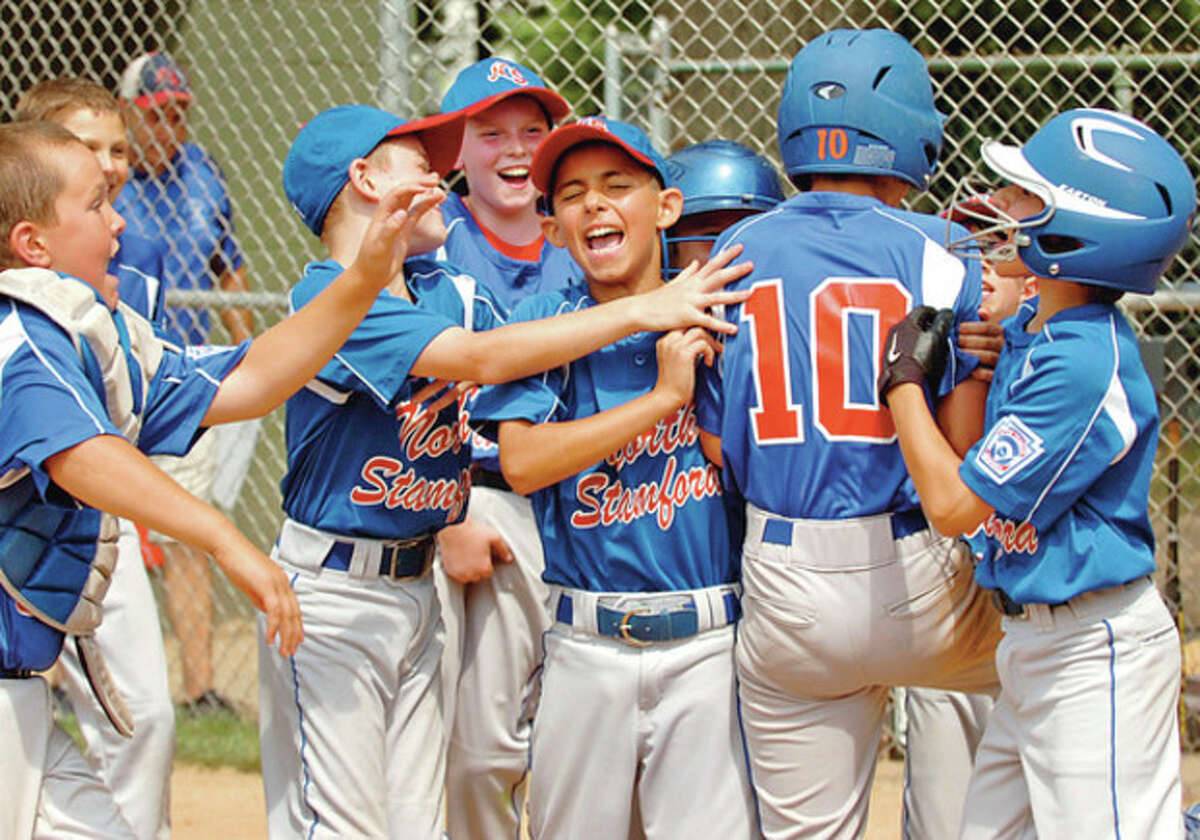 North Stamford's Adam Stone gets congratulated by his teammates after hitting a home run during the 9 and 10 year old Little League District 1 Championship against Wilton game in Darien Saturday. Hour photo / Erik Trautmann