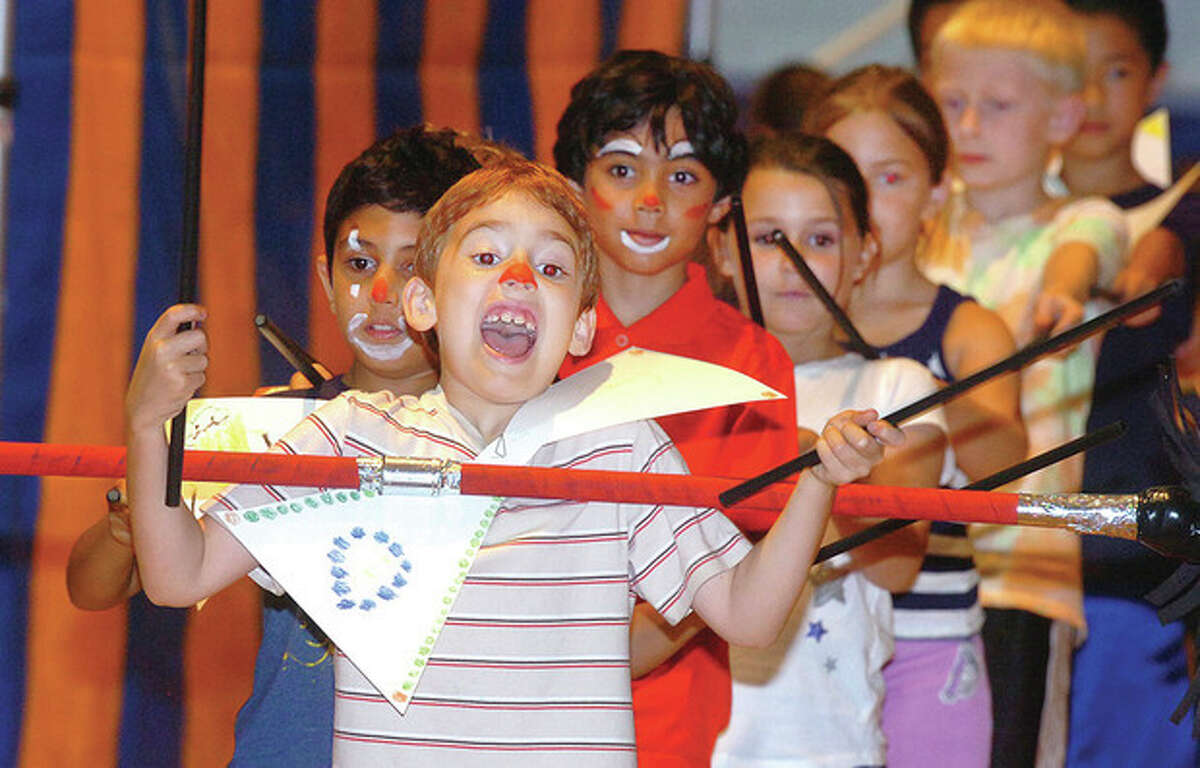 Above, Sebastian Shaw passes a large baton over his head to the next in line during the concluding performance at Our Lady of Fatima School's Circus Camp on Friday, July 13. At right, Amanda Jeffries helps her son Alex, 5, put on a giant, hand-colored bow tie before he performs at the camp. Photos by Alex von Kleydorff