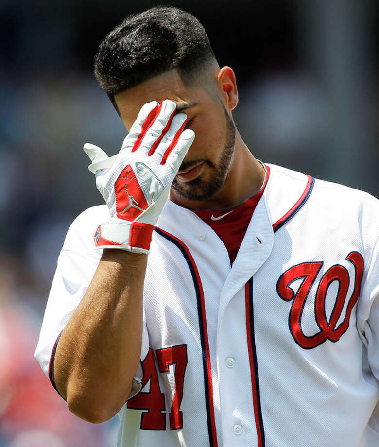 Washington Nationals starting pitcher Gio Gonzalez wipes his brow as he walks back to the dugout after grounding out in the third inning of a baseball game against the New York Mets on Thursday, July 19, 2012, in Washington. (AP Photo/Carolyn Kaster) / AP