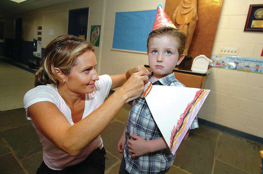 Hour Photo/ Alex von Kleydorff. 5 yr old Alex Jefferies has mom Amanda attach his hand colored giant clown bow tie before he performs at Circus Camp / 2012 The Hour Newspapers
