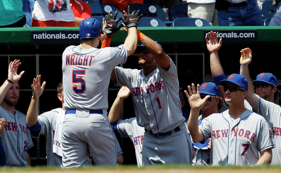 New York Mets' David Wright (5) is greeted by teammates including Jordany Valdespin (1) after hitting a two-run home run in the first inning of a baseball game against the Washington Nationals at Nationals Park, Thursday, July 19, 2012, in Washington. (AP Photo/Carolyn Kaster) / AP