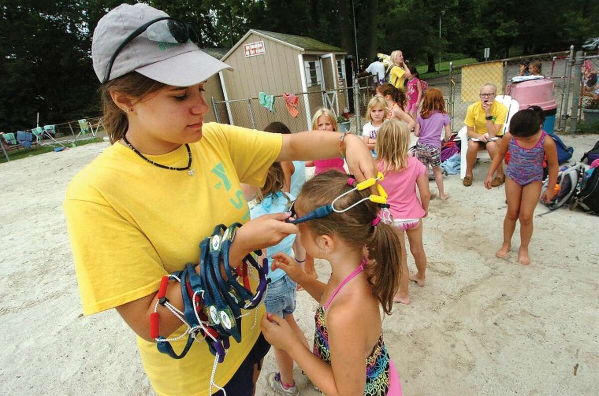 Hour Photo/ Alex von Kleydorff. Wilton Y Counselor Christine Gerhlein places Swimbands on the campers before they go swimming in the pond.