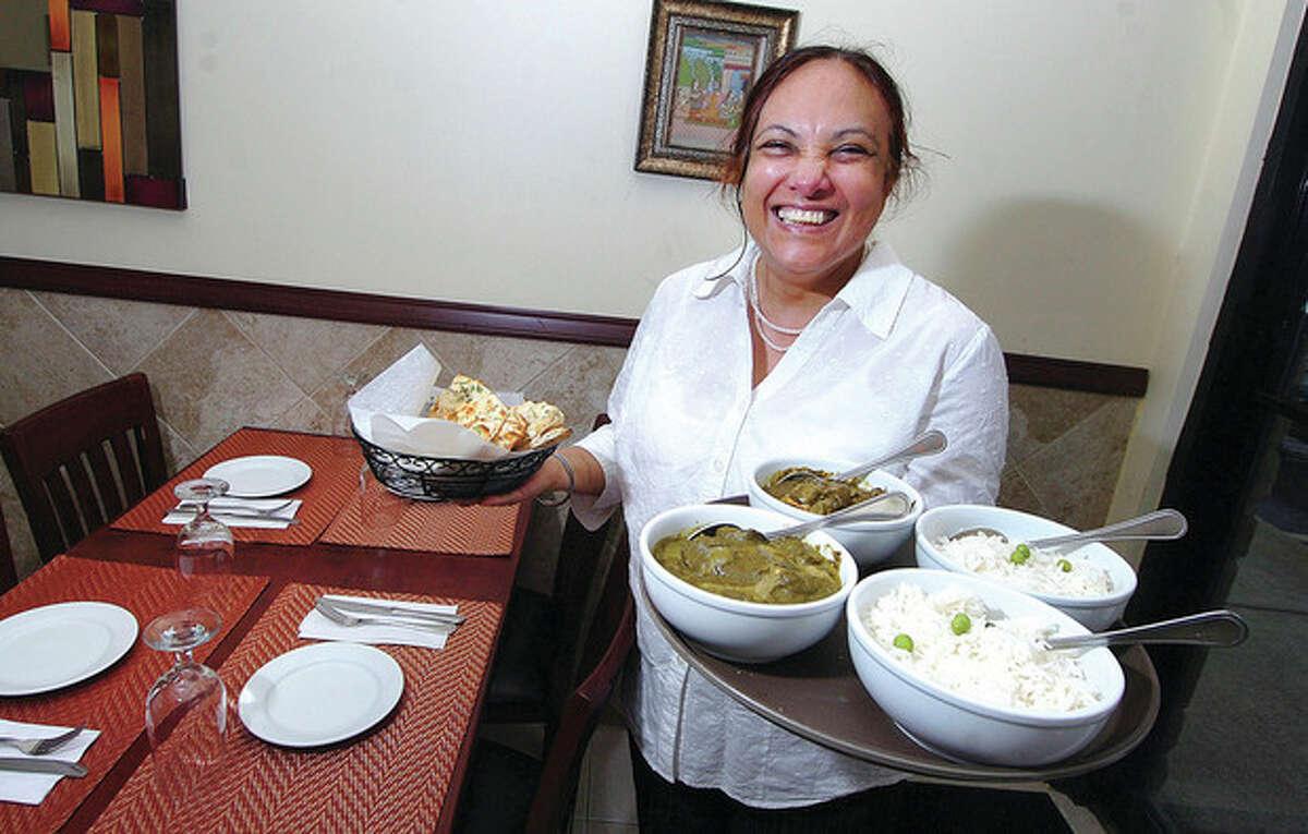 Hour photo/ Alex von Kleydorff Anterpreet Kaur, owner of Saffron Restaurant shows some of the entrees like Palak Paneer andf Saag Chicken
