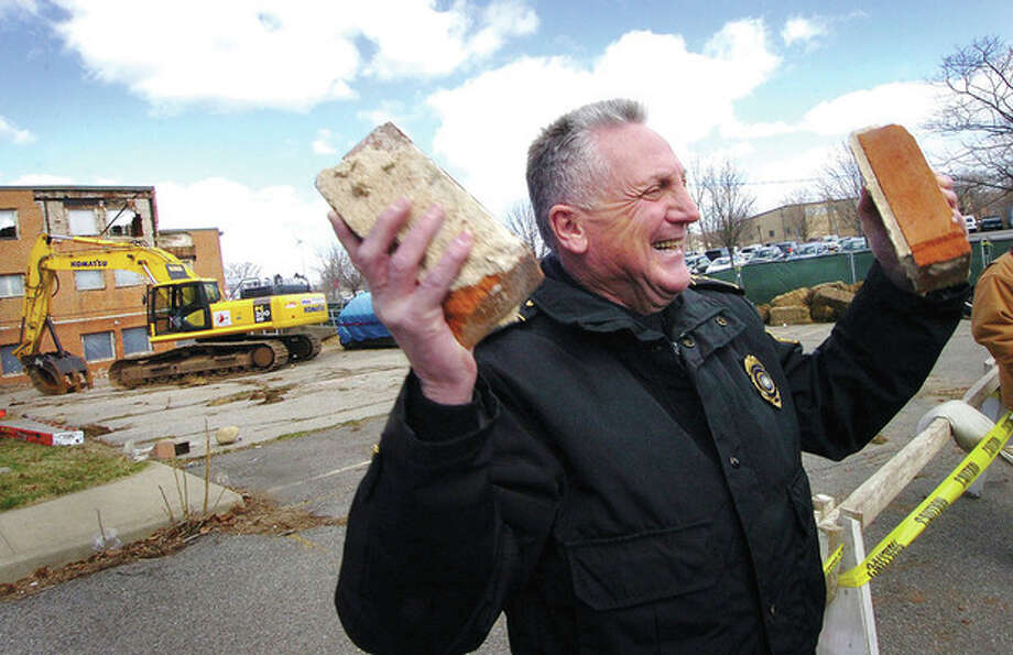 Photo/Alex von Kleydorff. Norwalk Police Chief Harry Rilling hoists two bricks brought down from the old Police headquaters building during a ceremony to begin demolition. / © 2011 The Hour Newspapers/Alex von Kleydorff
