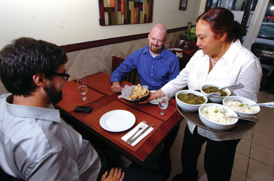 Hour Photo/ Alex von Kleydorff. Anterpreet Kaur, owner of Saffron serves some customers dinner ate her Norwalk restaurant / 2012 The Hour Newspapers