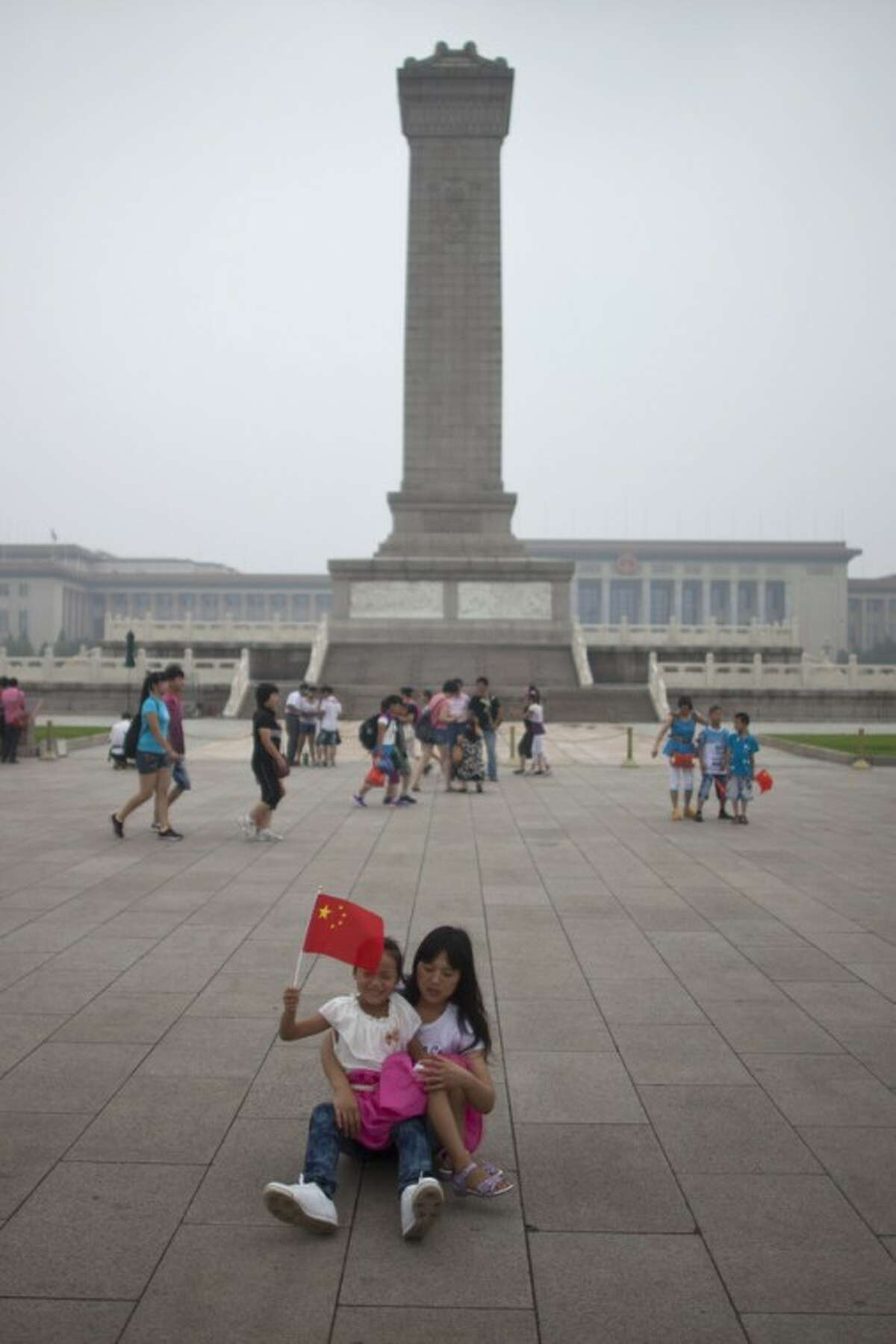 In this Monday, July 9, 2012 photo, a girl waves Chinese national flag while resting with her mom in front of the Monument to People's Heroes on the Tiananmen Square in Beijing, China. Tiananmen Square, the world's largest public square, is surrounded by buildings of political and cultural significance and is visited by thousands of tourists daily. (AP Photo/Alexander F. Yuan)