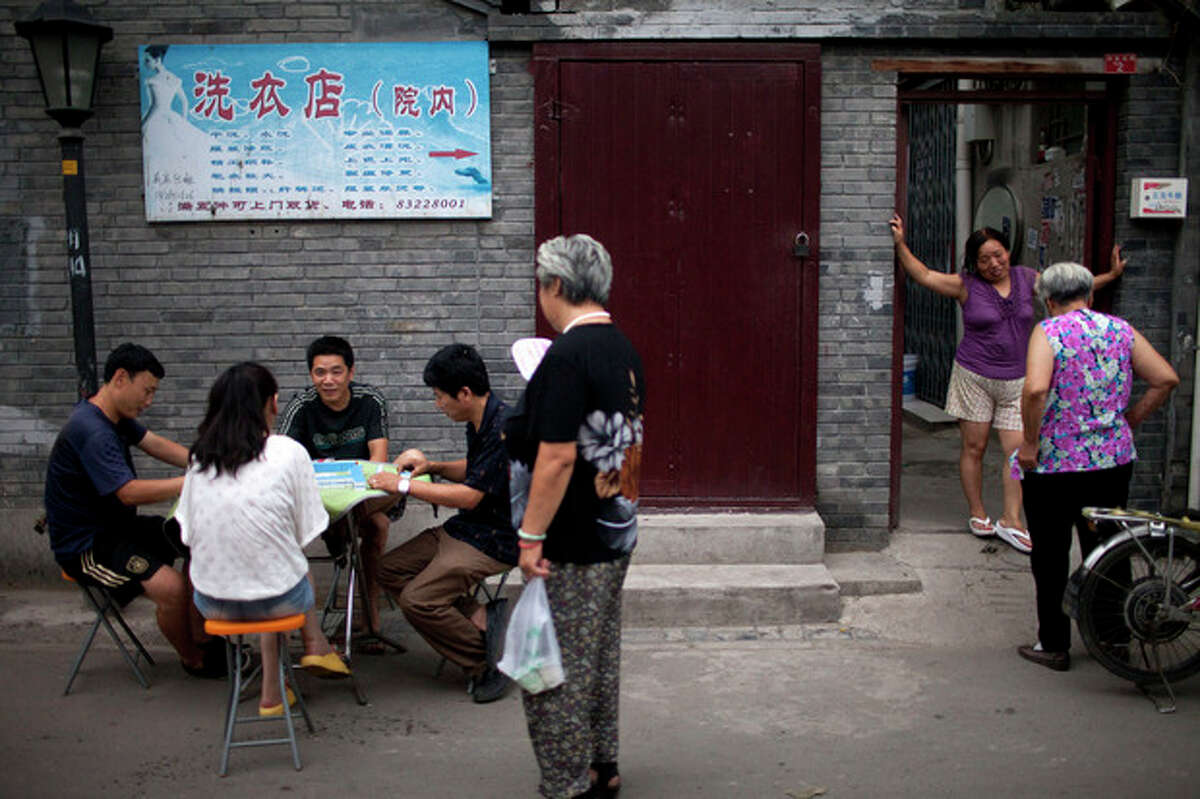 In this Sunday, July 8, 2012 photo, residents chat and play majhong after dinner time in a hutong, an old alleyway, near the Houhai lake in Beijing, China. To see a side of Beijing other than glitzy shopping malls or imposing, Soviet-style government buildings, take an afternoon to explore the city's ancient narrow alleyways, known as hutongs. (AP Photo/Alexander F. Yuan)