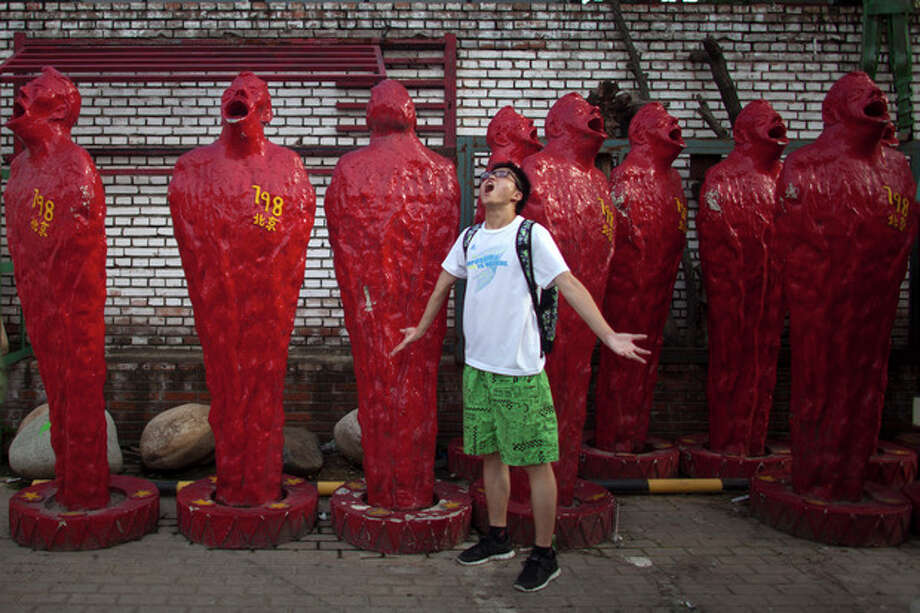 In this Thursday, July 12, 2012 photo, a man poses for photos in front of art pieces at the 798 Art District in Beijing, China. The city's art district, often compared to New York City's Greenwich Village, is a thriving community of about 400 galleries, shops and restaurants on the eastern edge of Beijing housed in a complex of former electronics factories built with the help of East Germany in the 1950s. (AP Photo/Alexander F. Yuan) / AP