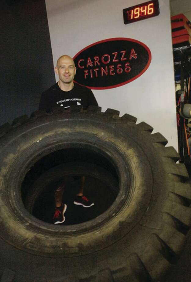 Michael Carozza of Carozza Fitness flips a 700 lb tire as part of the work out he prescribes for the Muffin Top Challenge, the contest he holds 3 times a year that could nab the winner $5000.