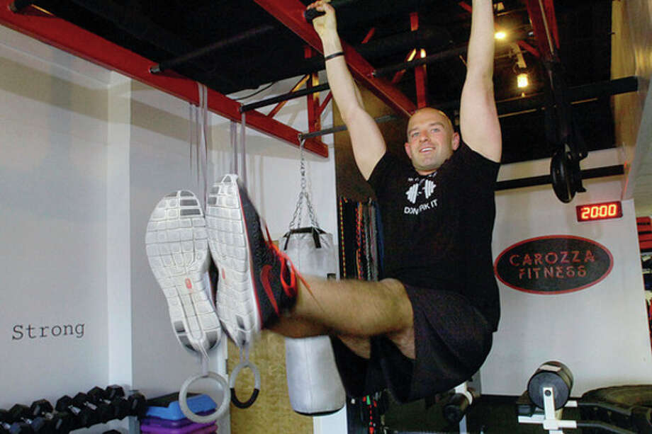 Hour photo / Erik Trautmann Michael Carozza of Carozza Fitness performs leglifts as part of the workout he prescribes for the Muffin Top Challenge, the contest he holds that could nab the winner $5,000. / (C)2011, The Hour Newspapers, all rights reserved