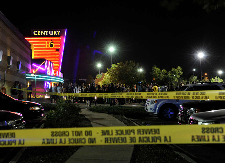 People gather outside the Century 16 movie theatre in Aurora, Colo., at the scene of a mass shooting early Friday morning, July 20, 2012. Police Chief Dan Oates says 14 people are dead following the shooting at the suburban Denver movie theater. He says 50 others were injured when gunfire erupted early Friday at the Aurora theater. Oates says a gunman appeared at the front of one of the Century 16 theaters. (AP Photo/The Denver Post, Karl Gehring) / The Denver Post