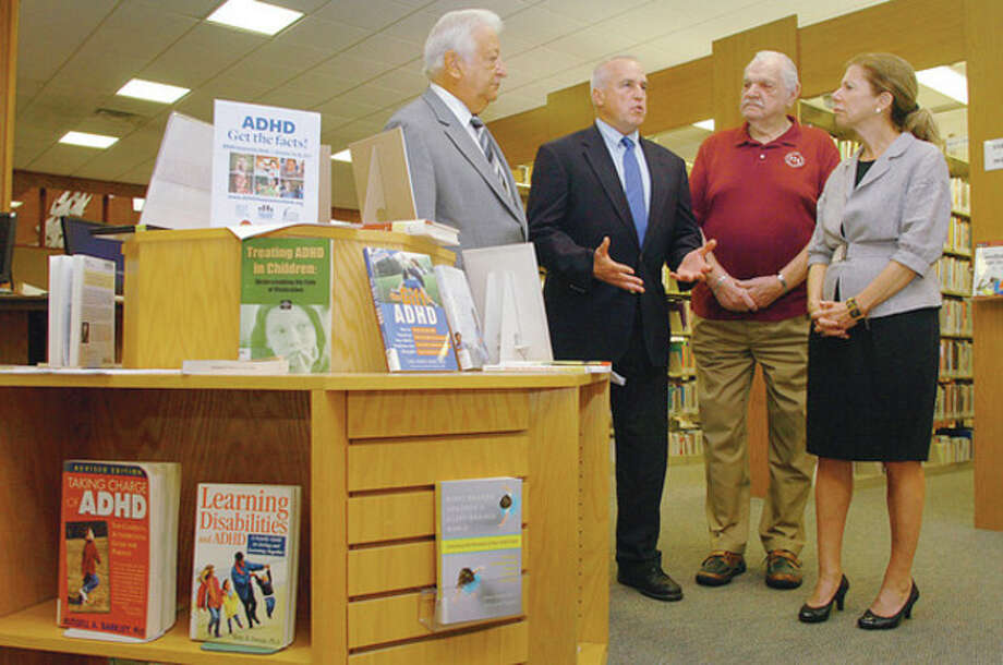 Hour photo / Erik Trautmann Jeffry Spahr, CACLD president, speaks after Mayor Richard Moccia, left, proclaimed Oct. 16 - 22 ADHD Awareness Week at the Norwalk Public Library, while Stanley M. Siegel, secretary of the library Board of Directors, and Christine Bradley, library director, look on Thursday. / (C)2011, The Hour Newspapers, all rights reserved