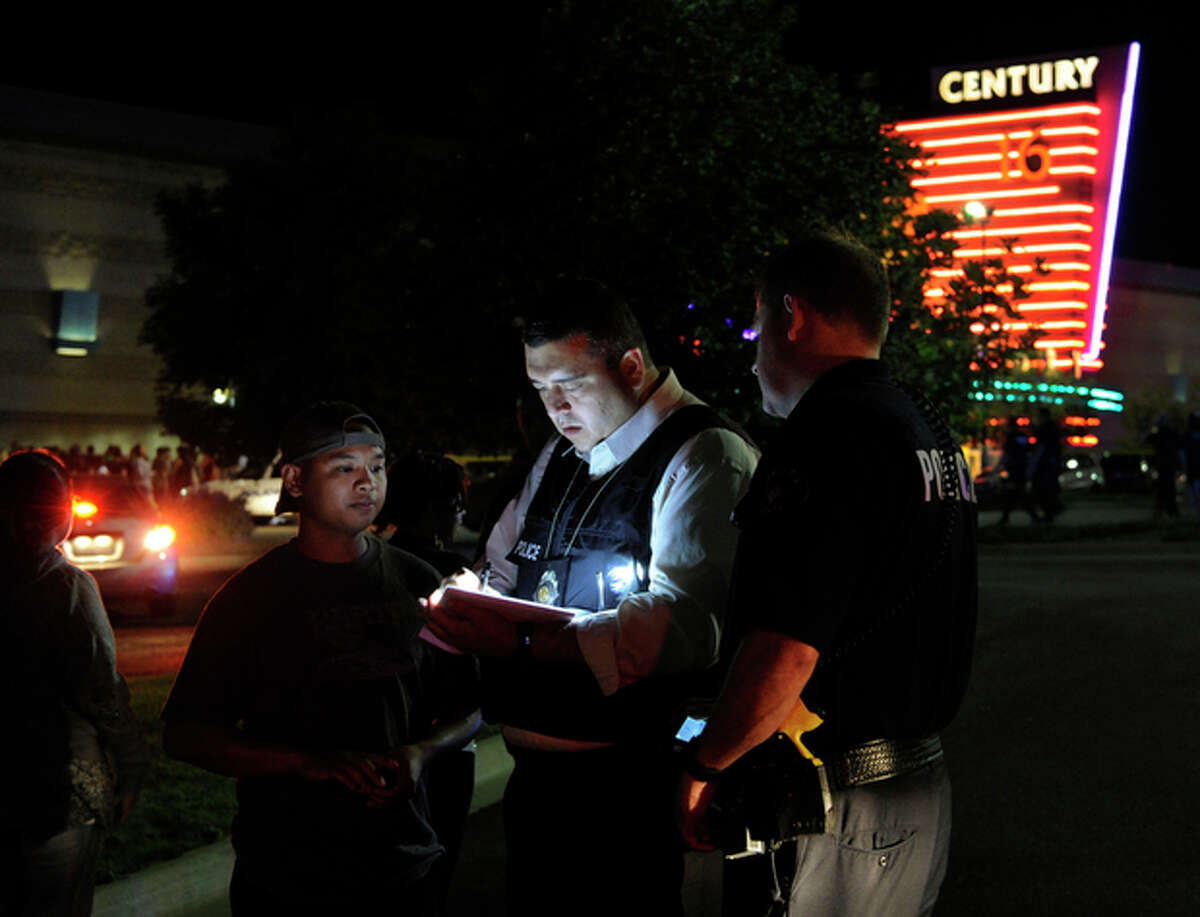 An Aurora Police Department detective takes a witness statement following a shooting Friday morning July 20, 2012. Aurora Police responded to the Century 16 movie theatre early Friday morning where police confirm at least 14 people are dead and 50 others injured. (AP Photo/Karl Gehring, The Denver Post)