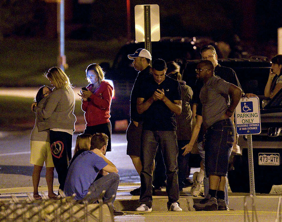 """People use mobile devices as they wait outside Gateway High School where witnesses were brought for questioning after a shooting at a movie theater showing the Batman movie """"The Dark Knight Rises,"""" Friday, July 20, 2012 in Aurora, Colo. A gunman wearing a gas mask set off an unknown gas and fired into the crowded movie theater killing 12 people and injuring at least 50 others, authorities said. (AP Photo/Barry Gutierrez)"""