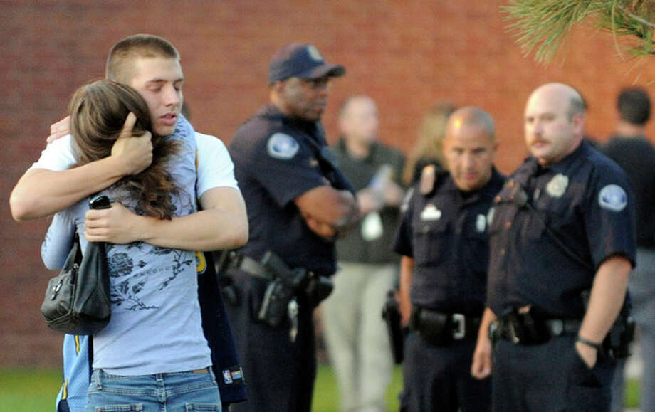 Eyewitness Jacob Stevens, 18, hugs his mother Tammi Stevens after being interview by police outside Gateway High School where witnesses were brought for questioning Friday, July 20, 2012 in Aurora, Colo. A gunman wearing a gas mask set off an unknown gas and fired into the crowded movie theater killing 12 people and injuring at least 50 others, authorities said. (AP Photo/The Denver Post, RJ Sangosti) TV, INTERNET AND MAGAZINES CALL FOR RATES AND TERMS / The Denver Post