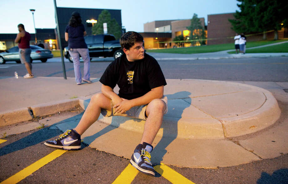 "Eyewitness Chandler Brannon, 25, sits outside Gateway High School where witnesses were brought for questioning after a shooting at a movie theater showing the Batman movie ""The Dark Knight Rises,"" Friday, July 20, 2012 in Aurora. A gunman wearing a gas mask set off an unknown gas and fired into the crowded movie theater killing 12 people and injuring at least 50 others, authorities said. (AP Photo/Barry Gutierrez) / FR170088 AP"