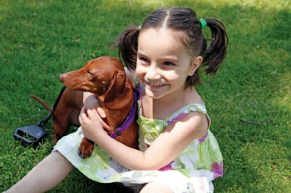 Kaitlyn Raiente, 4, sits with her dog Charlie during the 13th annual Dachshund Reunion held at Jesup Green in Westport Saturday afternoon. Hour Photo / Danielle Robinson