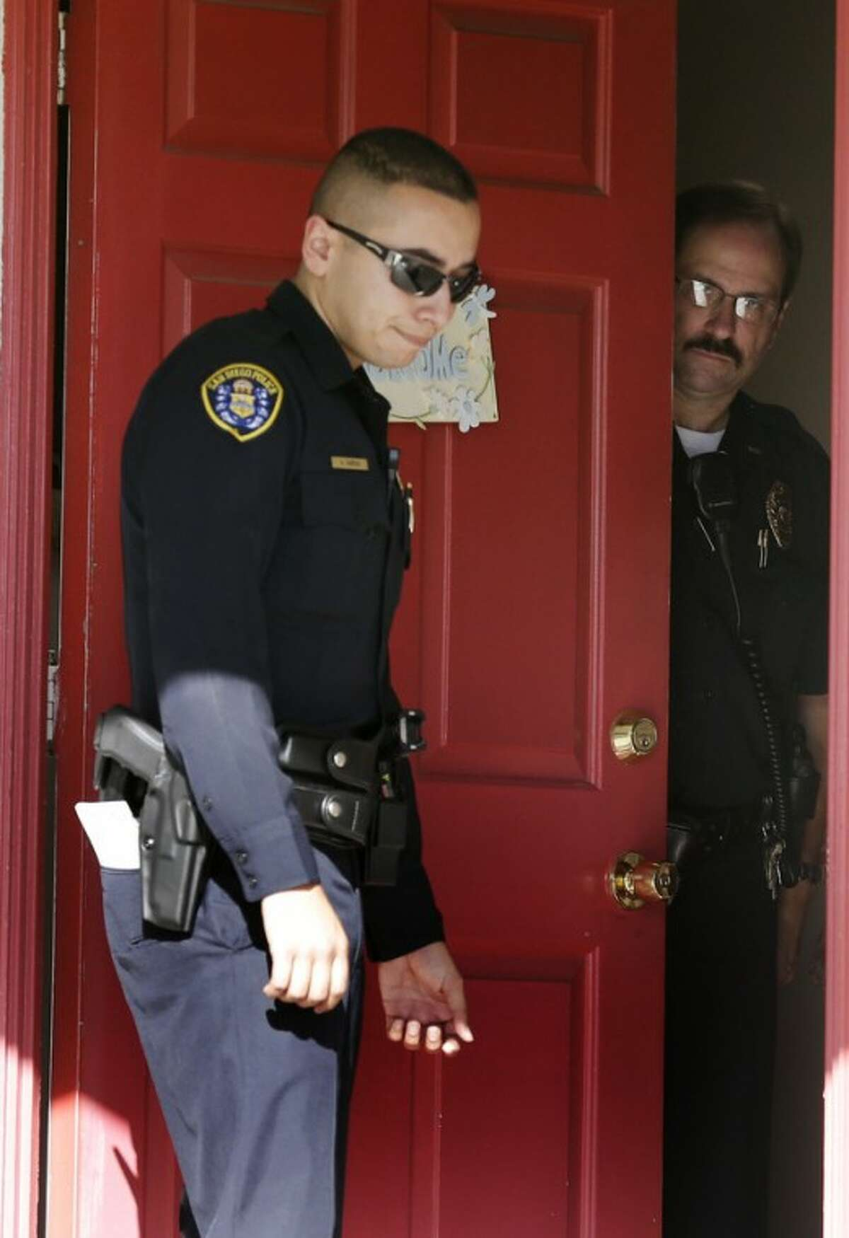 San Diego police officers stand in the doorway of the home of the mother of Colorado shooting suspect James Holmes Friday, July 20, 2012, in San Diego. A gunman in a gas mask barged into a crowded Denver-area theater during a midnight showing of the Batman movie on Friday, hurled a gas canister and then opened fire in one of the deadliest mass shootings in recent U.S. history. (AP Photo/Gregory Bull)