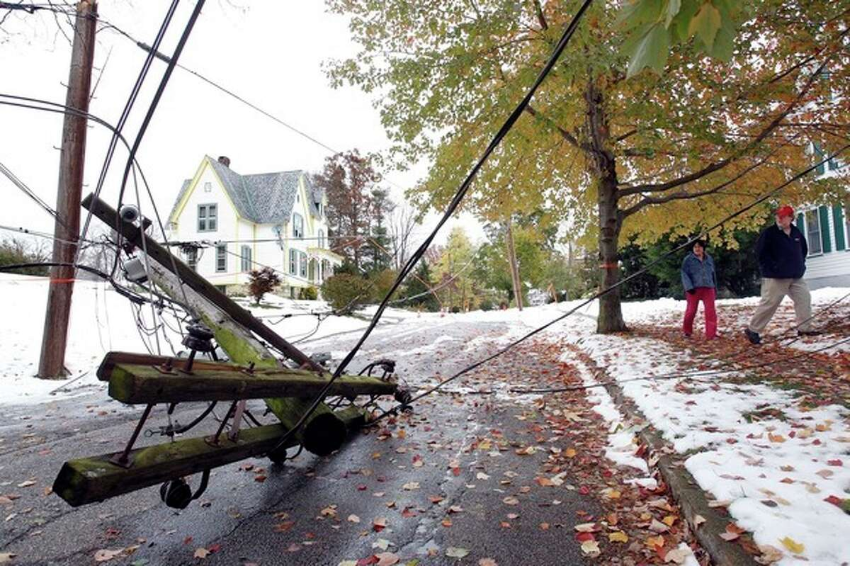 Residents look at a transformer that lies in the middle of Maple Ave. in Newton, N.J. Monday Oct. 31, 2011. An unusual October snow storm this past Saturday dumped up to 15 inches of snow in some areas of N.J. causing power outages across the state. (AP Photo/Rich Schultz)