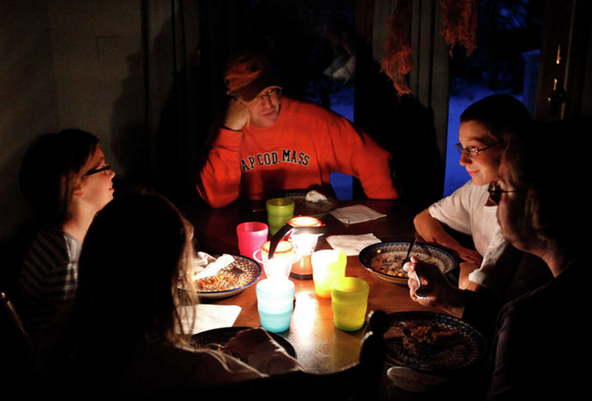 Members of the Ward family, of Wilbraham, Mass., from the left, daughters Melanie and Grace, father Chris, top, son Ben, and mother Tracey, eat dinner by the light of lanterns during a blackout in their Wilbraham home Monday, Oct. 31, 2011. The Wards have been without power since Saturday after snow and high winds from a rare late October storm brought down trees and tree limbs across the state, damaging power lines and leaving many without electricity. (AP Photo/Steven Senne)
