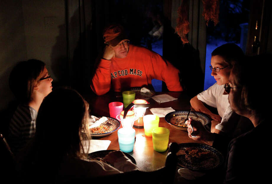 Members of the Ward family, of Wilbraham, Mass., from the left, daughters Melanie and Grace, father Chris, top, son Ben, and mother Tracey, eat dinner by the light of lanterns during a blackout in their Wilbraham home Monday, Oct. 31, 2011. The Wards have been without power since Saturday after snow and high winds from a rare late October storm brought down trees and tree limbs across the state, damaging power lines and leaving many without electricity. (AP Photo/Steven Senne) / AP