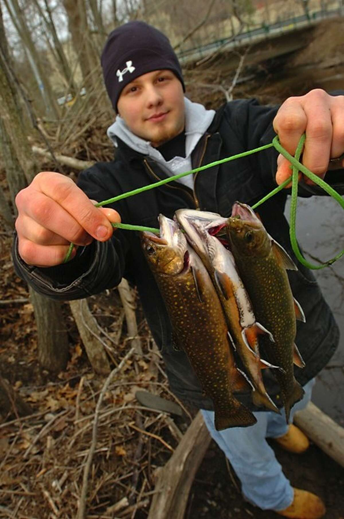 Chris Puglisi shows off his catch after fishing on the Norwalk River in Wilton Saturday during the opening day of trout season. Hour photo / Erik Trautmann
