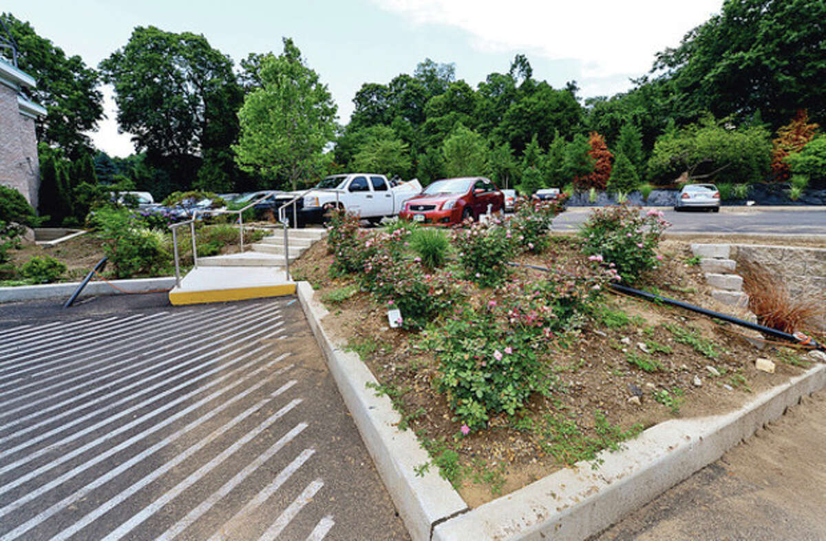 Chirs Handrinos and the Norwalk Inn has new trees, shrubs and other landscaping planted behind the rear parking area as buffer for neighbors. Neighbors are worried about the project and whether they will be adequately shielded from the expanding hotel on East Ave. Hour photo / Erik Trautmann