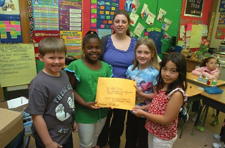 Dana Ross, center, with the Red Cross is presented with a check raised by Wolfpit Elementary students for tsunami and earthquake victims in Japan. From left, Brandon Frederec, Melissa Lewis, Abbey Liu and Mia Landzarotto. hour photo/matthew vinci