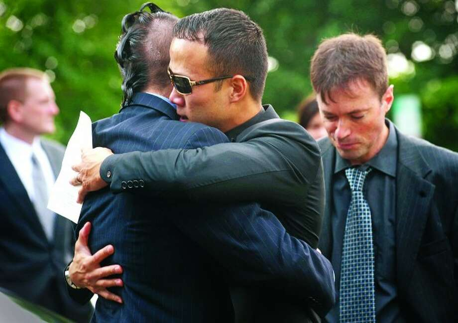 Friends and Catholic University Rugby teammates of the Neil Godleski, Ting Myauo and Peter Glover, embrace following Godleski''s funeral Thursday at St. Phillips Church in Norwalk. The 29 year old Norwalk native was shot to death in Washington D.C. Sunday during an apparent robbery attempt. Hour photo / Erik Trautmann