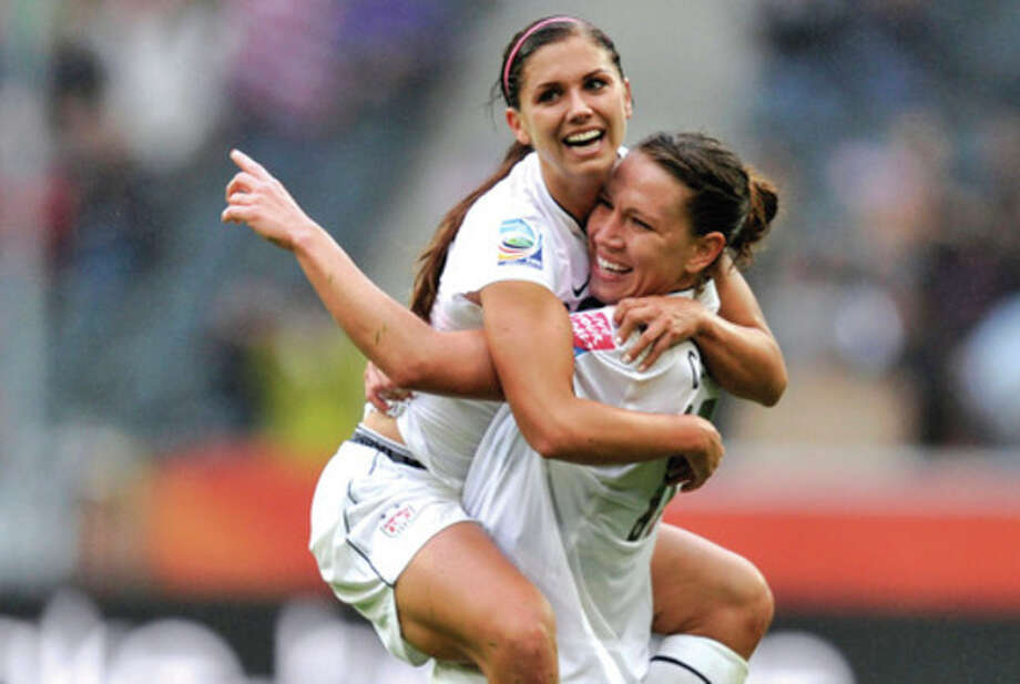 AP photo Alex Morgan is carried by U.S. teammate Lauren Cheney in celebration after she scored the third American goal in a 3-1 win over France in the WomenÕs World Cup semifinals. Cheney watched the U.S. win the 1999 World Cup as a youngster in the stands. Now sheÕs part of a team trying to build its own legacy. / AP