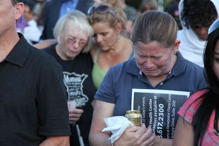 """People mourn at a vigil, Friday, July 20, 2012 in Aurora, Colo. Authorities report that 12 died and more than three dozen people were shot during an assault at the theatre during a midnight premiere of """"The Dark Knight."""" (AP Photo/Robert Ray) / AP"""