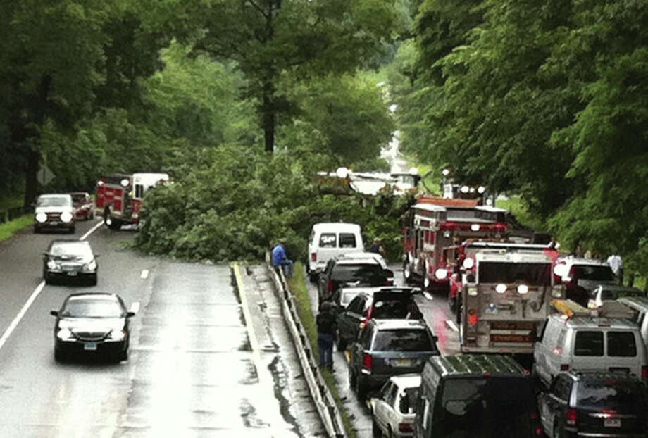 In this June 23, 2011 photo, rescue personnel work at the scene of a tree that fell onto the Merritt Parkway in Stamford, Conn., killing a Massachusetts man traveling along the roadway. Stately trees hugging the roadside are pretty but sometimes perilous, falling onto cars three times in recent weeks. (AP Photo/Stamford Advocate, Jack Nickerson) MANDATORY CREDIT / Stamford Advocate File Photo
