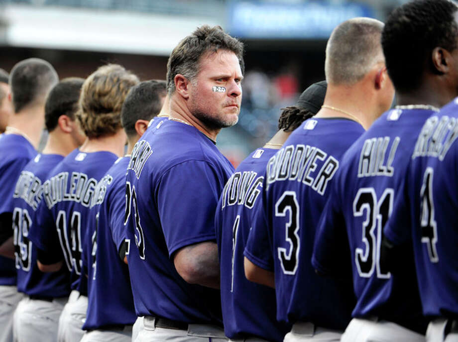 Colorado Rockies' Jason Giambi, center, looks out to the field as players observe a moment of silence for the victims of the Colorado theater shooting before the start of a baseball game against the San Diego Padres Friday, July 20, 2012, in San Diego. The gunman, identified by police as 24-year-old James Holmes, used a military-style semi-automatic rifle, a shotgun and a pistol, stopping only to reload. At least 12 people were killed and several dozens wounded in one of the deadliest mass shootings in recent U.S. history. (AP Photo/Denis Poroy) / FR59680 AP