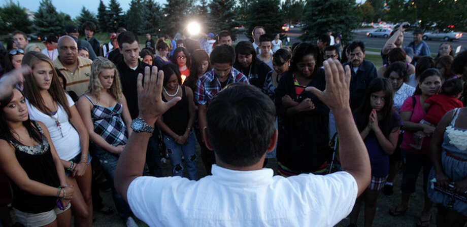 Phil Martinez, of Aurora, Colo., leads a prayer during a candle-light vigil, Friday, July 20, 2012, in Aurora, Colo., across the street from the movie theater where a gunman killed at least 12 people and wounded dozens of others Friday in one of the deadliest mass shootings in recent U.S. history. (AP Photo/Ted S. Warren) / AP