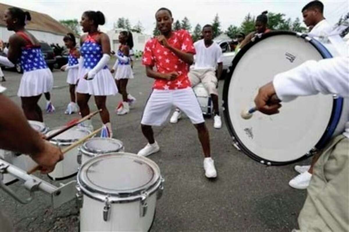 Jackie Thornton, of Hartford, center, dances with his group A.B.C. Another Bad Creation, before the annual West Indian parade, in Hartford, Conn., Saturday, Aug. 13, 2011. Parade organizers say encouragement from city officials and a desire to accommodate the growing Caribbean population led to the decision to bring Saturday's parade into Bushnell Park. (AP Photo/Jessica Hill)