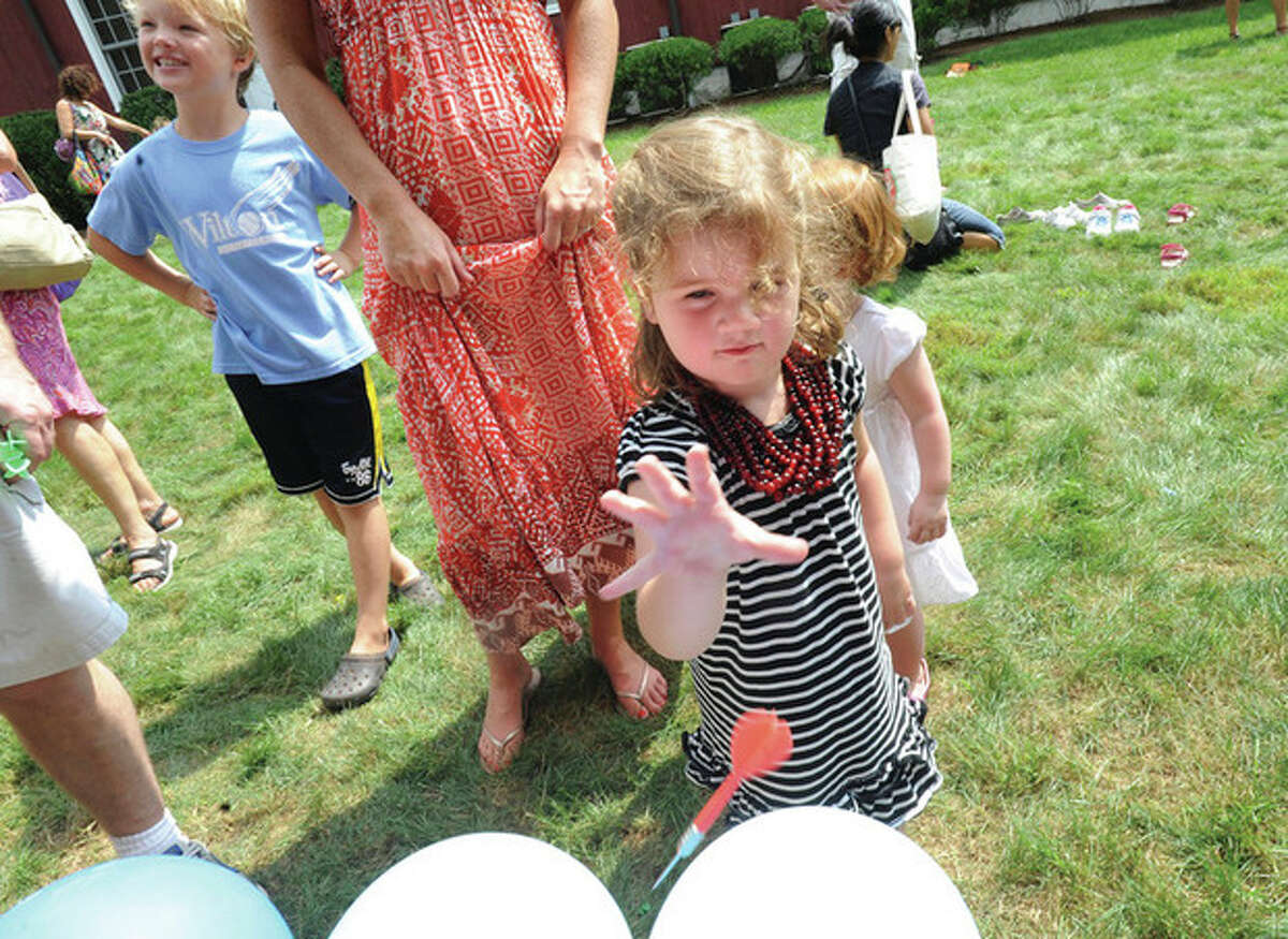 Lorelei Farber 3, plays a dart game Sunday in Wilton at the 79th annual Cannon Grange Agriculural Fair. hour photo/matthew vinci