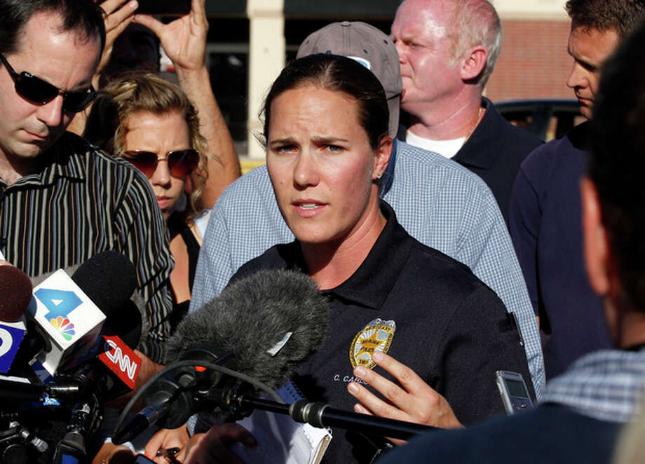 """Sgt. Cassidy Carlson, center, spokesperson for the Aurora Police Department, speaks during a media availability near the apartment of alleged gunman James Holmes, Saturday, July 21, 2012, in Aurora, Colo. Authorities reported that 12 people died and dozens more were shot during an assault at a movie theater midnight premiere of """"The Dark Knight Rises."""" (AP Photo/Alex Brandon) / AP"""