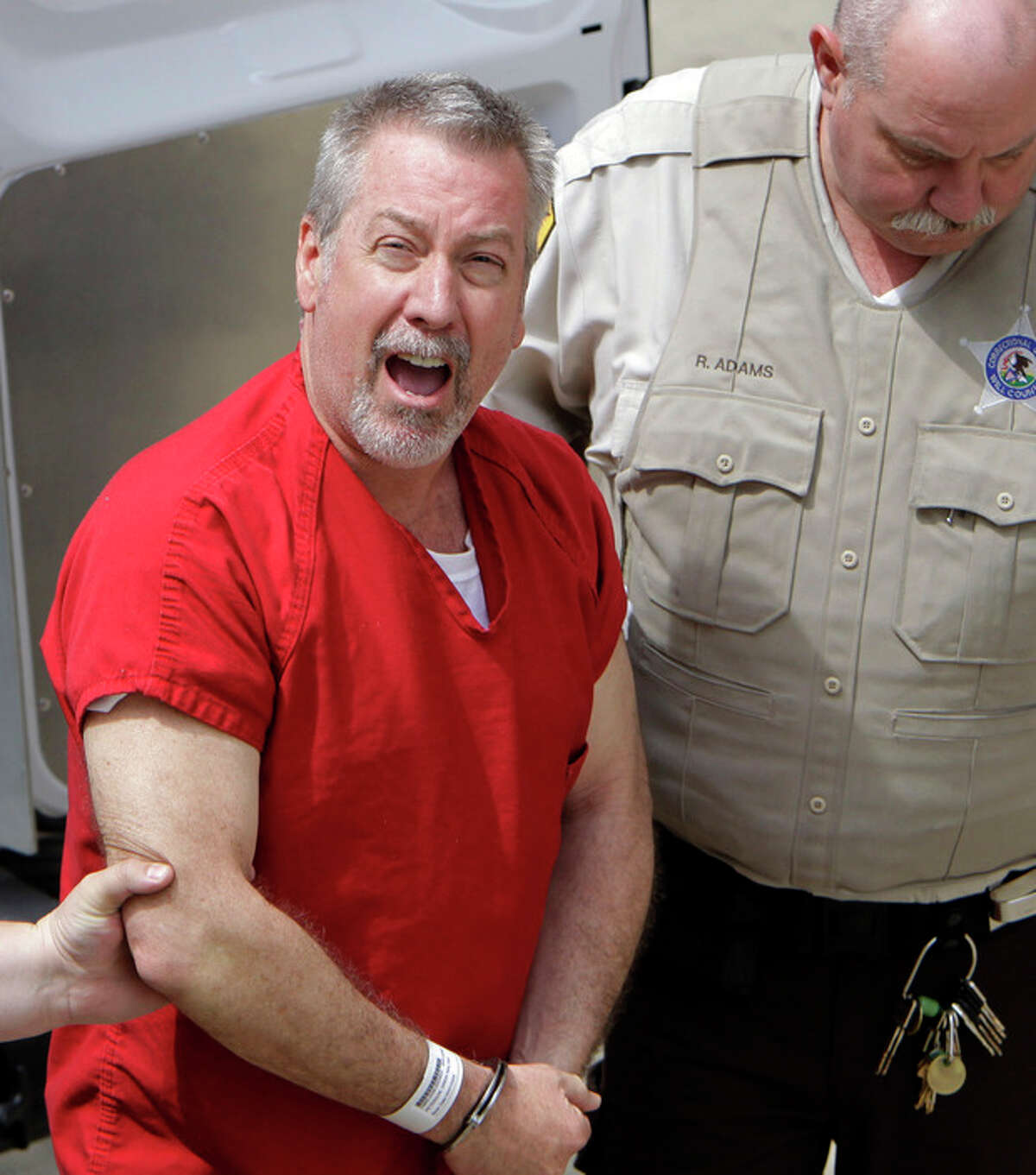 FILE - In this May 8, 2009 file photo, former Bolingbrook, Ill., police sergeant Drew Peterson yells to reporters as he arrives at the Will County Courthouse in Joliet, Ill., for his arraignment on charges of first-degree murder in the 2004 death of his former wife Kathleen Savio, who was found in an empty bathtub at home. Jury selection in his trial begins Monday, July 23, 2012. (AP Photo/M. Spencer Green, File)