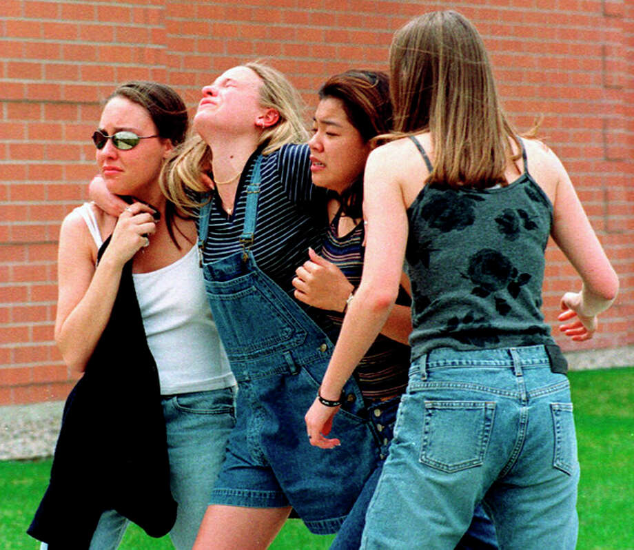 FILE - In this April 20, 1999, file photo unidentified young women head to a library near Columbine High School where students and faculty members were evacuated after two gunmen went on a shooting rampage in the school in the southwest Denver suburb of Littleton, Colo. Gun control advocates sputter at their own impotence. The National Rifle Association is politically ascendant. And Barack Obama's White House pledges to safeguard the Second Amendment in its first official response to the deaths of at least 12 innocents in a mass shooting at a new Batman movie screening in suburban Denver. Once, every highly publicized outbreak of gun violence produced strong calls from Democrats and a few Republicans for tougher controls on firearms. Now those pleas are muted, a political paradox that's grown more pronounced in an era scarred by Columbine, Virginia Tech, the wounding of a congresswoman and now the shootings in a suburban movie theater where carnage is expected on-screen only. (AP Photo/Kevin Higley, File) / AP