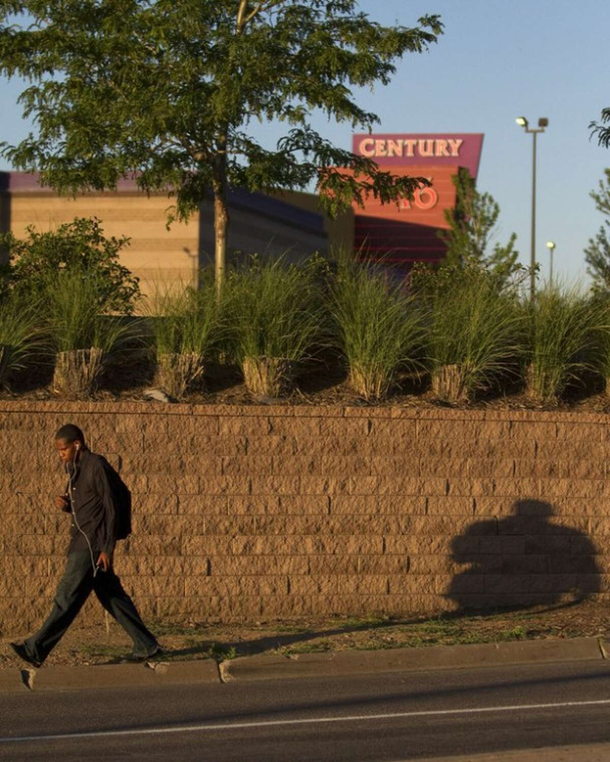 """A man walks by the Century Theater a day after a deadly shooting on Saturday, July 21, 2012 in Aurora, Colo. Twelve people were killed and dozens were injured in the attack early Friday at the packed theater during a showing of the Batman movie, """"Dark Knight Rises."""" Police have identified the suspected shooter as James Holmes, 24. (AP Photo/Barry Gutierrez)"""