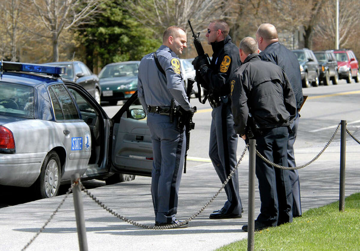 FILE - In this April 16, 2007, file photo, state and local police wait for a building to be cleared by police on the Virginia Tech campus in Blacksburg, Va., following a shooting incident. Gun control advocates sputter at their own impotence. The National Rifle Association is politically ascendant. And Barack Obama?'s White House pledges to safeguard the Second Amendment in its first official response to the deaths of at least 12 innocents in a mass shooting at a new Batman movie screening in suburban Denver. Once, every highly publicized outbreak of gun violence produced strong calls from Democrats and a few Republicans for tougher controls on firearms. Now those pleas are muted, a political paradox that?'s grown more pronounced in an era scarred by Columbine, Virginia Tech, the wounding of a congresswoman and now the shootings in a suburban movie theater where carnage is expected on-screen only. (AP Photo/Don Petersen)